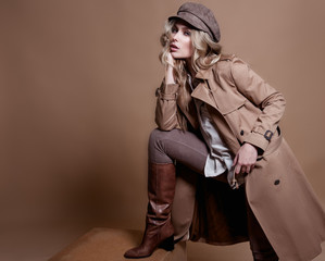 High fashion portrait of stylish blond woman in total beige look over beige background.