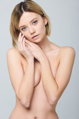 blonde naked woman posing isolated on grey