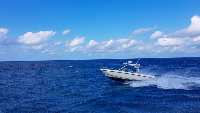 Speed fishing tender boat jumping the waves in the sea and cruising the blue ocean day in Bahamas. Blue beautiful water
