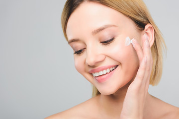 beautiful smiling young woman applying cosmetic cream on face isolated on grey