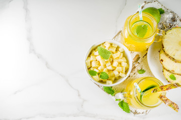 Cold pineapple mojito cocktail with ice, lime and mint, rustic wooden background copy space
