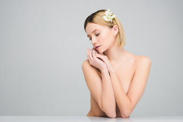 attractive blonde girl posing with freesia flowers in hair, isolated on grey