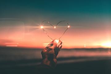 Simbolo del cuore fatto con striscia di luci led tenuto in mano di fronte a un tramonto sull'oceano. San Valentino e festa della donna concetto. - fototapety na wymiar