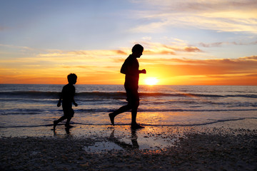 Silhouette of Father and his Young Son Jogging on Beach Together at Sunset
