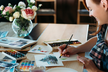 Watercolor painting. Artist at work. Smiling female painter doing color mix brushstrokes. Sketches and palette supplies around.