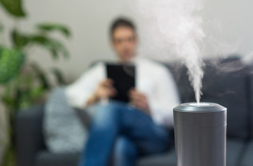 Air humidifier at living room. Man using tablet pc on the background.