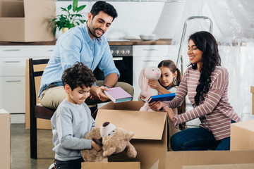 happy latin family unpacking boxes in new home