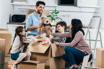 cheerful latin father holding soft toy near hispanic family while unpacking boxes in new home Wall mural