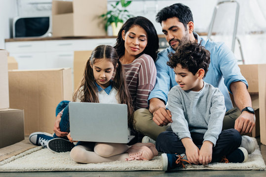 cheerful latino family looking at laptop while sitting on carpet in new home