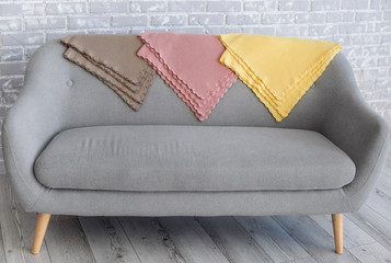 Gray, pink and yellow plaids are decorated with lace on the back of a gray sofa.