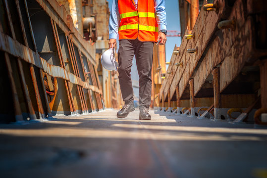 legs wearing safety shoe of the worker or engineering step on the walkway channel to returning the station after works done conpleted, tired, upset, job trouble, headache in job