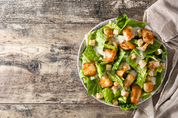 Caesar salad with lettuce,chicken and croutons on wooden table. Top view. Copyspace