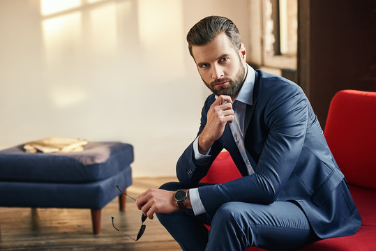 Close-up portrait of a handsome businessman in a suit who is sitting on sofa at office and looking at the camera