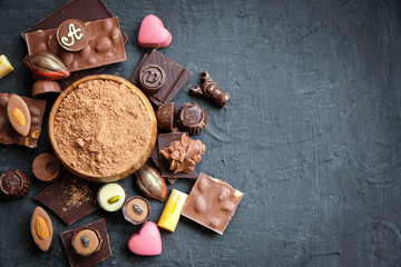 Assorted chocolate and cocoa powder on black background