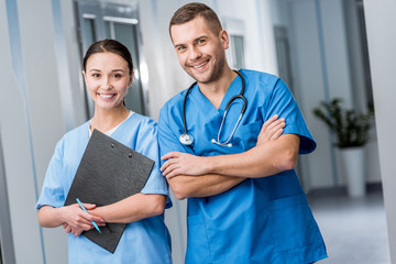 Smiling doctors in blue uniform holding stethoscope and clipboard