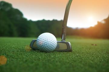 golf club and golf ball close up in grass field with sunset. Golf ball close up in golf coures at Thailand
