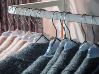 Clothes hang on a shelf in a designer clothes store