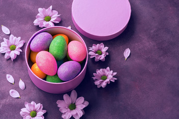 Colorful shiny Easter eggs in a round gift box on purple background decorated with flowers. Overhead view,copy space