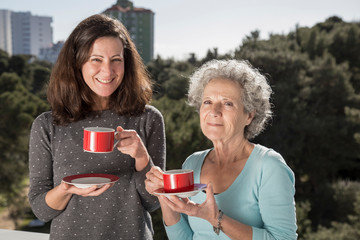 Portrait of happy senior mother and her daughter with tea cups