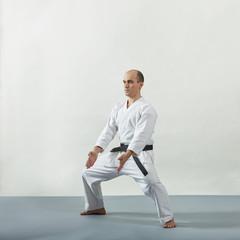 Athlete in karategi doing formal exercises on gray cover