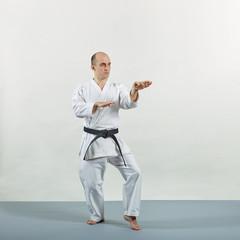 Athlete in karategi trains formal exercises on gray cover