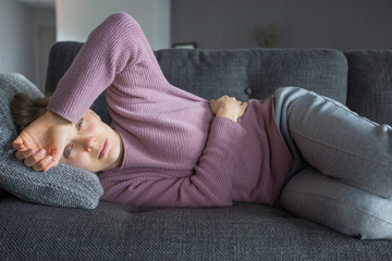 Sick woman lying on sofa, holding hands on stomach and head