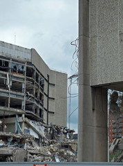 a large destroyed collapsing building with exposed walls and smashed floors falling into rubble and tangled debris