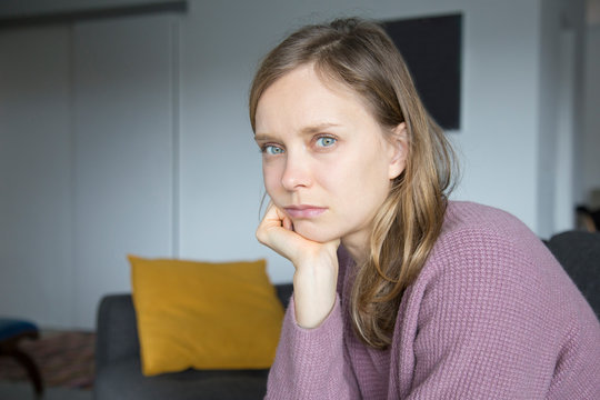 Upset young woman sitting on sofa at home, looking at camera
