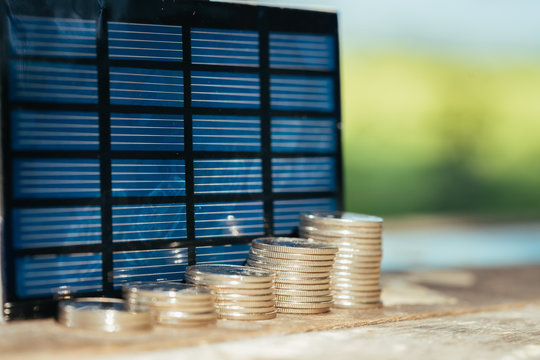 Solar panel, photovoltaic, alternative electricity source - selective focus, copy space with coin stacks. Success, dealing, greeting and partner concept.
