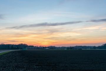 Farbenprächtiger Sonnenuntergang über Feldern. Standort: Deutschland, Nordrhein-Westfalen, Borken
