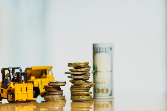 Financial And Macro Economic Concept, pile of coins money stacked on wooden table, with construction vehicle and equipment. Vintage tone.