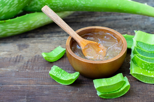 Fresh aloe vera plant, stem slices and gel on wooden background, skin therapy concept