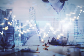 Hands typing on laptop. Business and Financial concept. Double exposure of stock market charts.