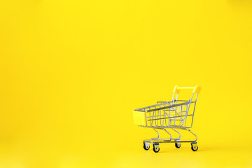 Shopping cart trolley basket is empty on a bright yellow background. Conception Festive Sale Discount. Trading Supermarket Retail.Copy space .