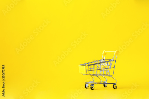 Shopping cart trolley basket is empty on a bright yellow