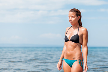 Young woman in a bikini wet from swimming in the sea