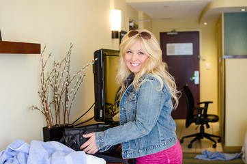Blonde woman in a hotel room packs up a small suitcase as she prepares to leave the lodge, Concept for vacation
