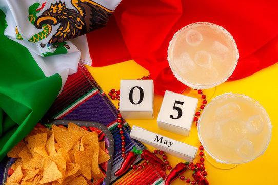 Mexican fiesta and Cinco de Mayo party concept theme with block calendar set on May 5th, jalapeno pepper beads necklace, traditional rug or serape, two margarita glasses, chips and the mexican flag