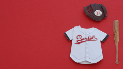 White baseball jersey, glove and bat laying flat on a red background with writing space