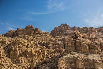 desert bare steep rocks foreshortening from below on vivid blue sky background
