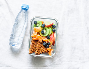 Foto op Canvas Assortiment Healthy food snack sweet vitamin lunch box and bottle of clean water on a light background, top view. Peanut butter toast, apples, kiwi, tangerines, blueberry lunch box