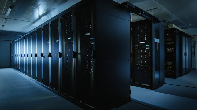 Shot of a Working Data Center With Rows of Rack Servers. Led Lights Blinking and Computers are Working. Dark Ambient Light.