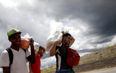 Venezuelans walk back to their country after buying food in the Brazilian border city of Pacaraima