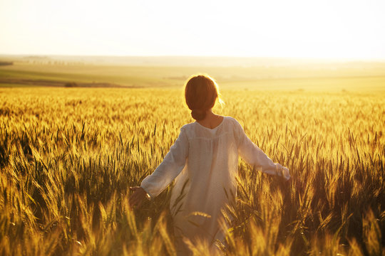 Happy woman walks over wheat field in the rays