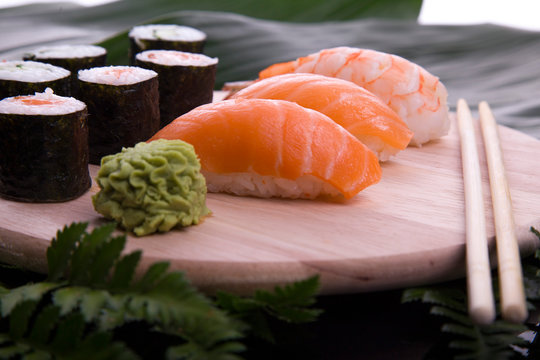 set of sushi on a wooden board with leaves of plants on a dark background