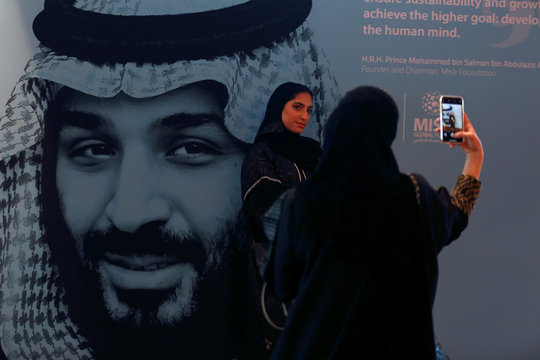 Participants take photos next to a picture of Saudi Crown Prince Mohammed bin Salman during the Misk Global Forum in Riyadh