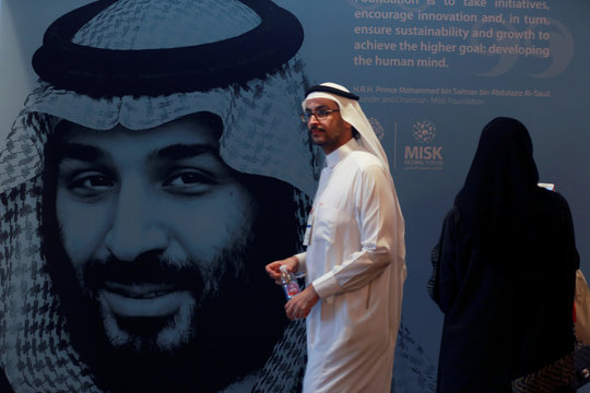 A participant walks next to a picture of Saudi Crown Prince Mohammed bin Salman during the Misk Global Forum in Riyadh