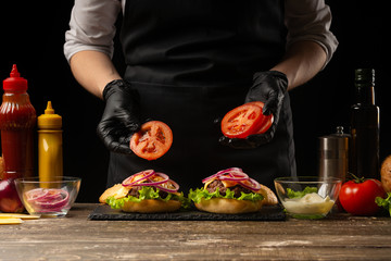 Chef puts tomato rings on a burger, on the background of the ingredients. Horizontal photo, Tasty and unhealthy food, fast food, homemade recipes, restaurant, catering, recipe book