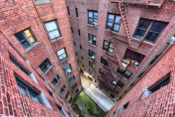 High angle, looking down view on illuminated brick apartment condo building architecture in Fordham Heights center, Bronx, NYC, Manhattan, New York City with fire escapes, windows