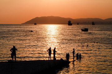 people and sunset on the sea